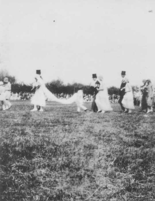 Parade group with a wedding theme in a field (bride with train and pageboy