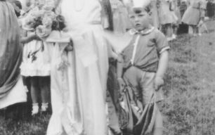 A young carnival queen with a reluctant pageboy, in a field