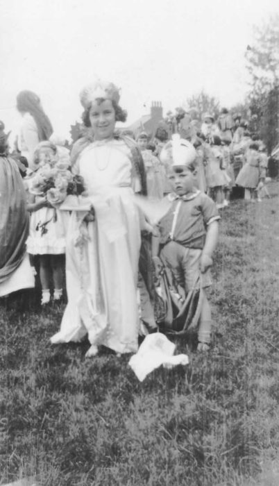 A young carnival queen with a reluctant pageboy