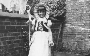 Girl dressed up as Bo Peep, in a back garden