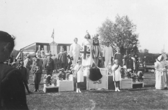 Parade group on a podium in a field featuring Britannia along with airmen