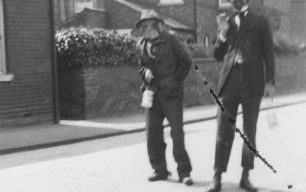 Two men, dressed up, in a street.
