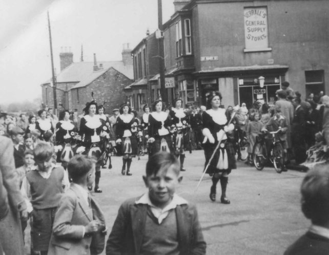 The Dagenham Girl Pipers lead a parade round New Bradwell