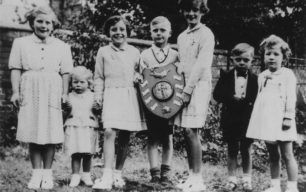 Young Wood Street residents with the trophy for best decorated street on the occasion of the 1953 Coronation