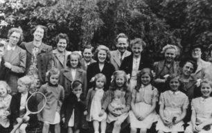 Group of children, men and women in a garden.