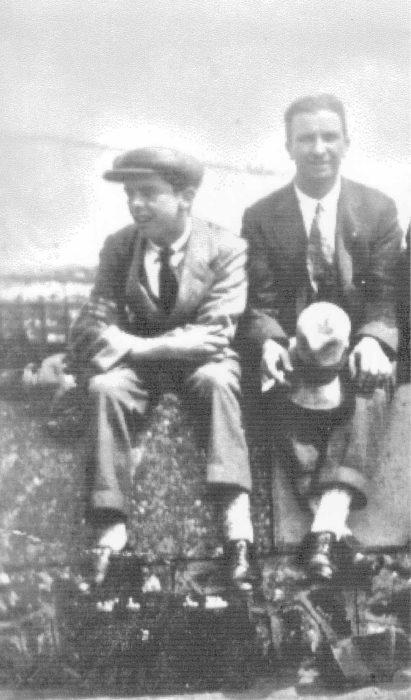 Two men seated on wall.