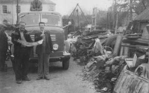 Goodmans Yard. Bernard Goodman on a lorry, Derek & John in front, with a fish. Johnny on left