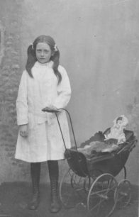 Postcard of girl with doll in pram.