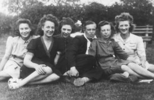 Group of six sitting on the grass incl. Audrey Willison.