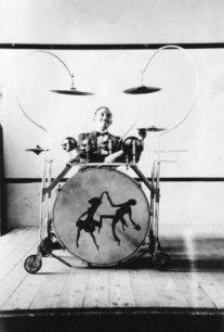 Drummer, with unusual drum kit on wheels.