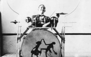 Drummer, with unusual drum kit on wheels.