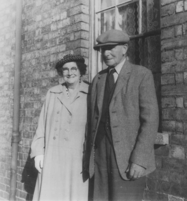 Couple outside a house.