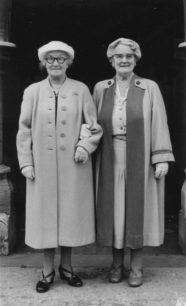 Two ladies, smartly dressed in coats.