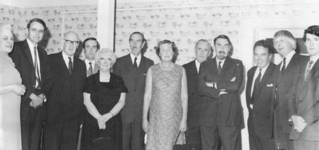Group of men and women in formal dress.