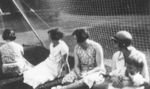 Ladies sitting against netting.