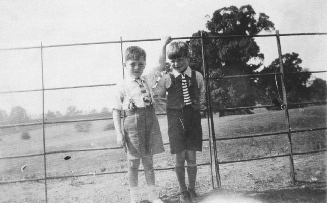 Ron Shouler and cousin with their backs to the fence at the cricket ground