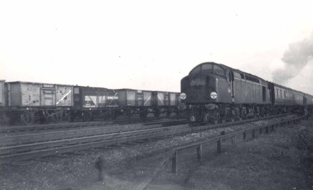 A diesel engine pulling carriages past goods trucks
