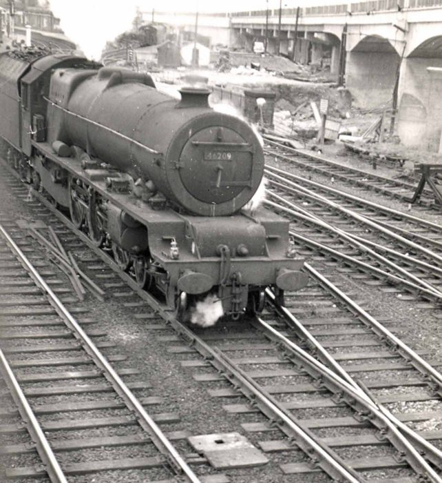 Steam engine pulling a freight train near the flyover