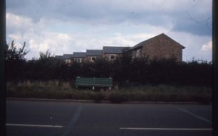 Green bench near boxy houses
