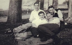 Four young men seated by a road