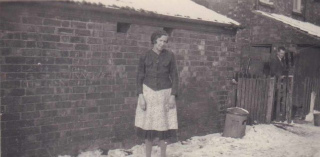 Woman in snowbound backway terrace